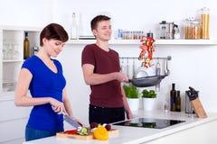 Frau, die das Gemüse und Mann leicht schlagen Nahrung in der Wanne hackt lizenzfreies stockfoto