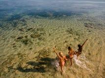 Junge Frauen, die in das Meer laufen stockfotos
