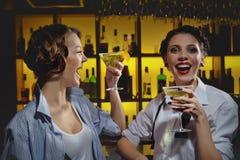 Junge Frauen, die an der Bar trinken Stockbild