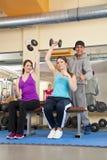 Junge Frauen, die in der Gymnastik mit Kursleiter trainieren Lizenzfreie Stockfotos