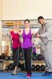 Junge Frauen, die in der Gymnastik mit Kursleiter trainieren Lizenzfreie Stockfotografie