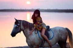 Junge Frauen, die ein Pferd reiten Stockbilder
