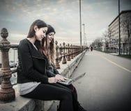 Junge Frauen, die einen Laptop betrachten stockfotografie