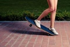 Junge Frauen, die einen Trick auf einem Skateboard tun lizenzfreie stockbilder