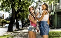 Junge Frauen, die Eiscreme essen Stockfotografie