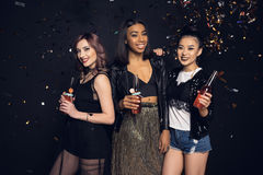 Junge Frauen, die Flaschen Alkoholgetränke halten und an der Kamera lächeln Stockfoto