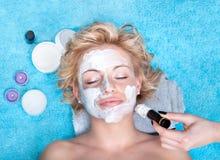 Junge Frauen, die Gesichtsschablone erhalten. lizenzfreie stockbilder
