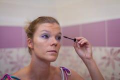 Junge Frauen, die ihre Augen mit Wimperntusche herrichten Stockfotografie