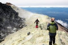 Junge Frauen, die in Krater des aktiven Vulkans gehen Stockbilder