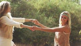Junge Frauen, die lachendes herum spinnen tanzen stock video