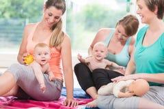 Junge Frauen, die Massage für ihre Babys üben Stockfoto