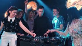 Junge Frauen, die mit dem DJ in einem Nachtklub tanzen und flirten stock video footage