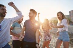 Junge Frauen, die mit ihren Freunden auf Strand tanzen stockbilder