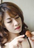 Junge Frauen, die Puderpinsel schauen Stockbilder