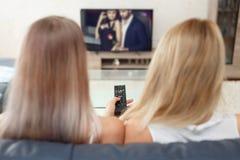 Junge Frauen, die romantischen Kanal in Fernsehen aufpassen Stockfoto