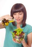 Junge Frauen, die Salat auf weißem Hintergrund machen Lizenzfreies Stockbild