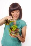 Junge Frauen, die Salat auf weißem Hintergrund machen Stockfotografie