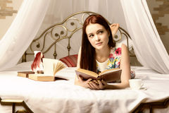 Junge Frauen, die Tee trinken und zu Hause ein Buch auf einem Bett lesen Stockfoto