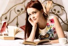 Junge Frauen, die Tee trinken und zu Hause ein Buch auf einem Bett lesen Lizenzfreie Stockfotos