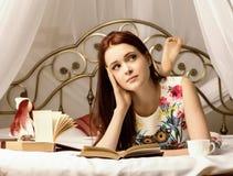 Junge Frauen, die Tee trinken und zu Hause ein Buch auf einem Bett lesen Lizenzfreies Stockfoto