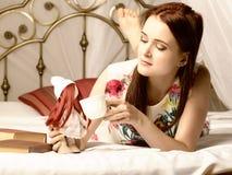 Junge Frauen, die Tee trinken und zu Hause ein Buch auf einem Bett lesen Lizenzfreie Stockfotografie
