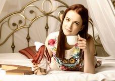 Junge Frauen, die Tee trinken und zu Hause ein Buch auf einem Bett lesen Stockbild