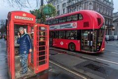 Junge Frauen, die am Telefon in der Telefonzelle in London sprechen Stockfotografie