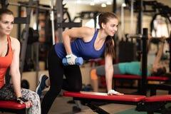 Junge Frauen, die Training in der Turnhalle mit Dummköpfen haben Stockfotografie