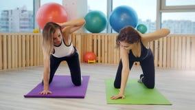 Junge Frauen, die Yoga im Studio tun Der Trainer stellt dar, dass eine neue Übung und eine junge Frau ihn wiederholt stock video
