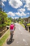 Junge Frauen fährt während des Zyklo Ausflugs der Reisfelder in Bali rad Lizenzfreie Stockfotos