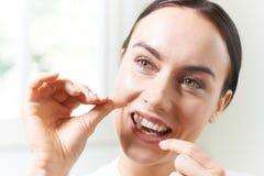 Junge Frauen-Flossing Zähne im Badezimmer Stockbilder