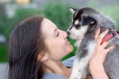 Junge Frauen hält ihren kleinen Haustierwelpen des besten Freunds des Schlittenhunds in ihren Armen Liebe für Hunde Lizenzfreie Stockfotografie