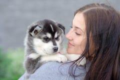 Junge Frauen hält ihren kleinen Haustierwelpen des besten Freunds des Schlittenhunds in ihren Armen Liebe für Hunde lizenzfreie stockbilder