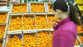 Junge Frauen-kaufende Tangerinen in einem Supermarkt stock footage