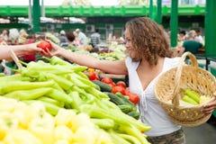 Junge Frauen-kaufende Tomate am Lebensmittelgeschäft-Markt Lizenzfreie Stockfotos