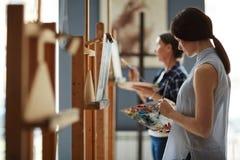 Junge Frauen-mischende Farben auf Palette beim Malen in Art Class Stockfoto