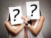 Junge Frauen mit Befragungsymbolen Stockfotografie