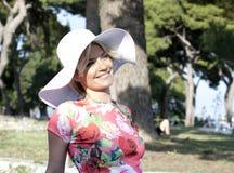 Junge Frauen mit dem weißen Hut, der im Park aufwirft Stockfotos