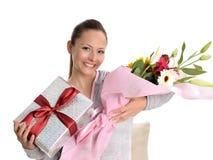 Junge Frauen mit Geschenk und Blumen Stockfoto