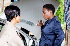 Junge Frauen nahe einem Auto in einer Garage lizenzfreie stockbilder