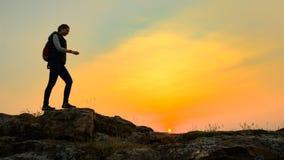 Junge Frauen-Reisender, der mit Rucksack auf Rocky Trail bei warmem Sommer-Sonnenuntergang wandert Reise- und Abenteuerkonzept lizenzfreie stockfotos