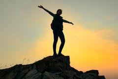 Junge Frauen-Reisender mit dem Rucksack, der auf die Oberseite des Felsens bei Sommer-Sonnenuntergang steht Reise- und Abenteuerk lizenzfreie stockfotografie