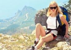 Junge Frauen-Reisender mit dem Rucksack, der auf felsiger Klippe des Gebirgsgipfels mit Vogelperspektive von Meer sich entspannt Stockbild