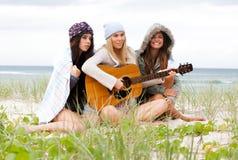 Junge Frauen am Strand mit einer Gitarre Lizenzfreie Stockfotografie