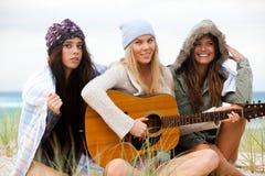 Junge Frauen am Strand mit einer Gitarre Lizenzfreies Stockfoto