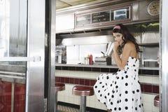 Junge Frauen-trinkende Erschütterung im Restaurant lizenzfreies stockbild