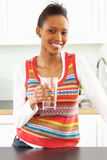Junge Frauen-trinkendes Glas Wasser in der Küche Stockfotos