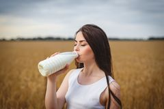 Junge Frauen trinkt erotisch Milch auf einem Gebiet Lizenzfreie Stockfotos