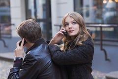 Junge Frauen und Männer, die auf Handy sprechen Lizenzfreies Stockfoto