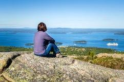 Junge Frauen-Wanderer, der auf einem Felsen sitzt Stockfotos